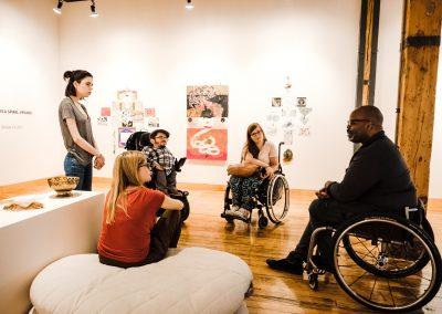 Das Team der Leidmedien und die Macher*innen der Gallerie sitzen bzw. stehen im Kreis und unterhalten sich. Es sind fünf Personen zu sehen.