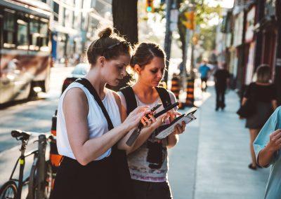 Zwei Frauen schauen während einer Mapping-Tour auf ihr Smartphone.