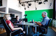 Lili und Judyta sitzen mit Jeff Dobbin in einem TV-Studio mit Green Screen zusammen.