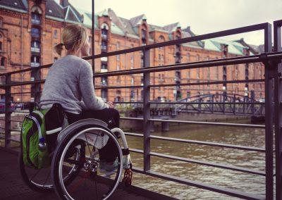 Eine Rollstuhlfahrerin steht in der Hamburger Speicherstadt auf einer Brücke und schaut auf die Elbe. Sie schaut über ein Geländer hinweg.