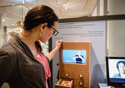 Eine Frau mit Hörgeräten schaut sich Videos in Gebärdensprache in einer Ausstellung im Deutschen Historischen Museum an.