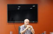 David Lepofsky sitzt an einem Tisch und hat die Ellenbogen auf dem Tisch und die Hände gefaltet. Im Hintergrund ist ein riesiger schwarzer Bildschirm an der Wand zu sehen.