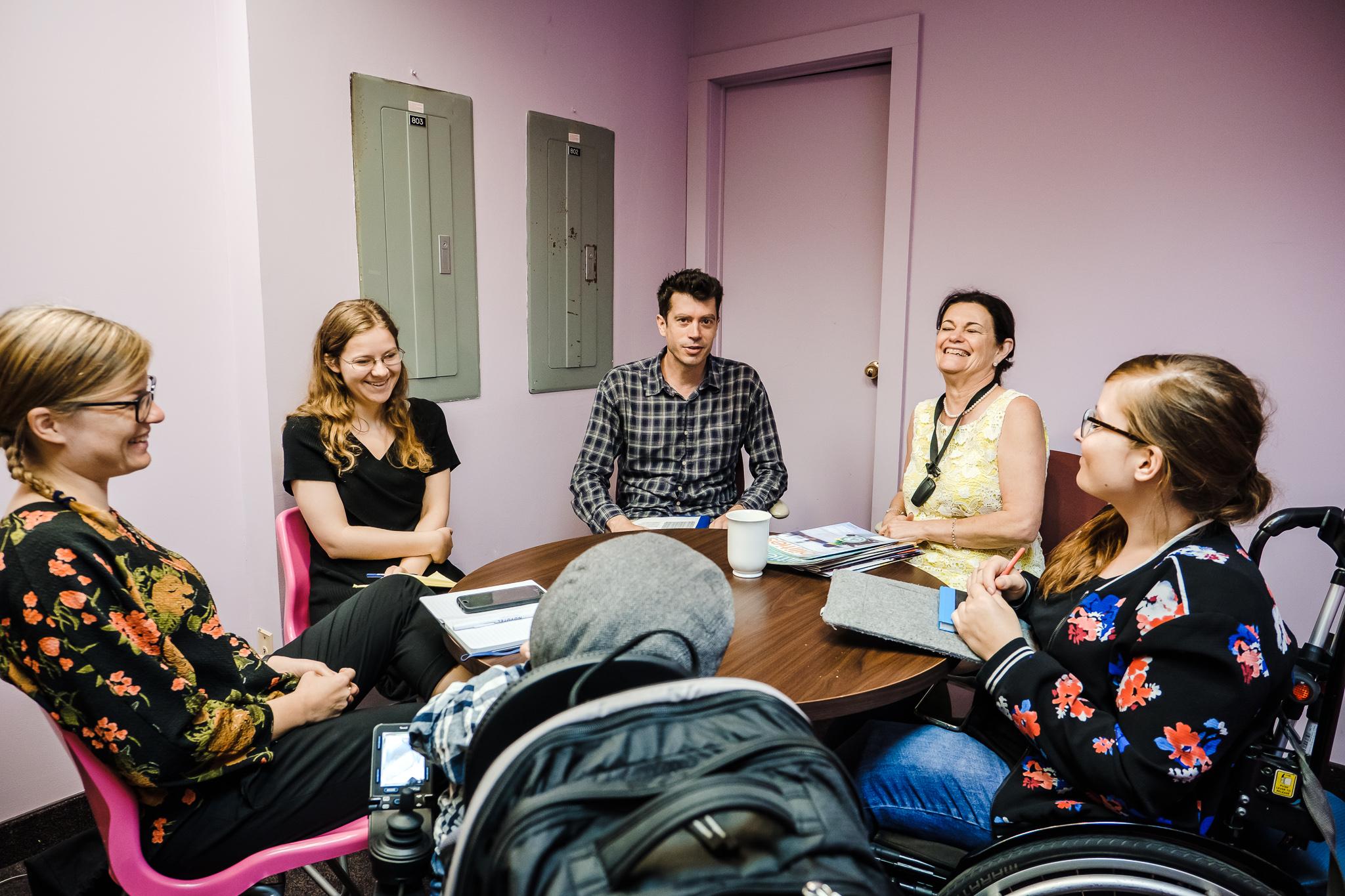 Lili, Raul und Judyta von Leidmedien sitzen am Tisch mit Mitarbeiter*innen vom Abilities Magazine.