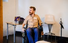 Luke Anderson ist zu sehen. Er sitzt im Rollstuhl und hat lockige, rote Haare. Er trägt ein helles Hemd und eine Jeans.