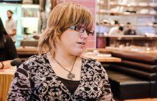 Melissa Graham hat mittellange blonde Haare, trägt eine Brille und ein gemustertes Oberteil. Sie sitzt im Rollstuhl.