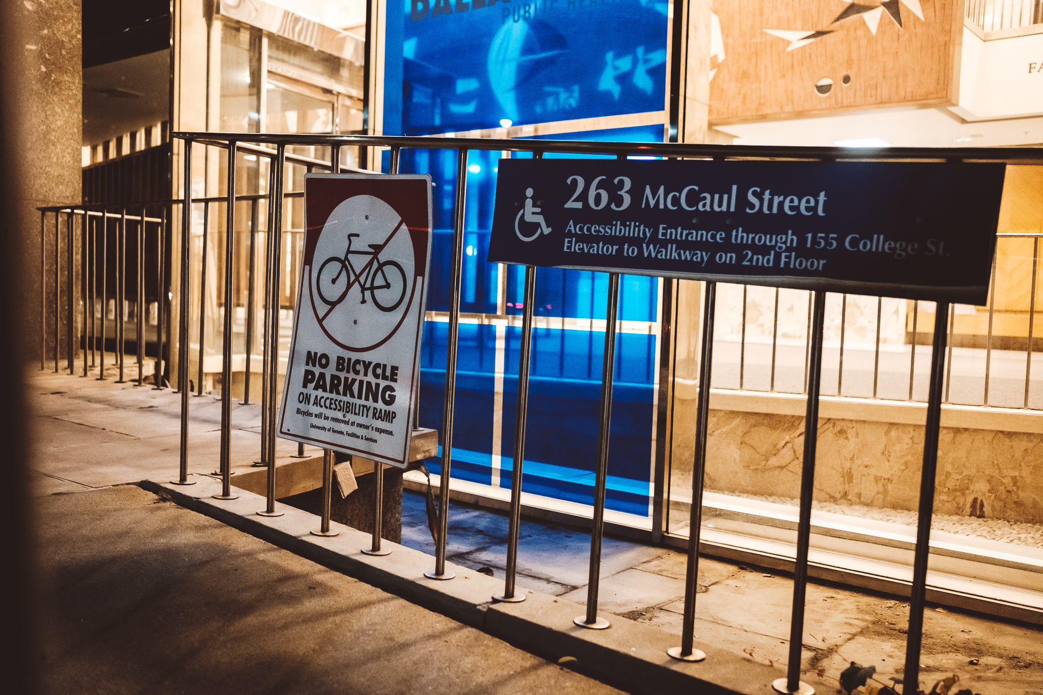 Ein Eingang zur U-Bahnstation ist zu sehen. Am Geländer ist ein Schild mit einem Rollstuhlsymbol mit der Information wo sich der nächste Aufzug befindet.