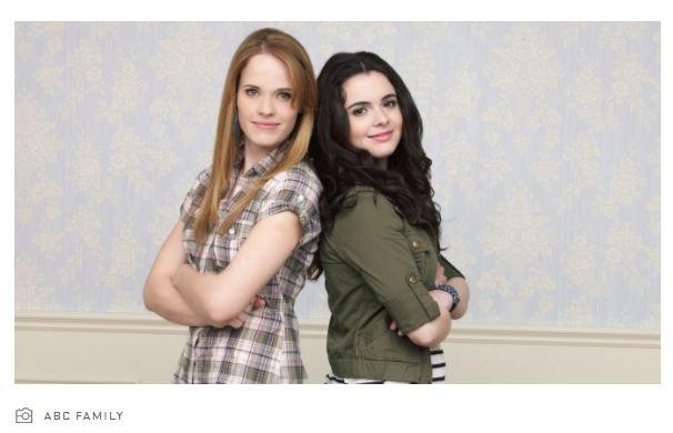 Zwei junge Frauen stehen Rücken an Rücken. Die Frau links hat blonde Haare und trägt ein kariertes Hemd. Die Frau rechts hat braune Haare und trägt ein grünes Hemd. Sie lächeln.