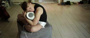 Ein junger Mann sitzt auf dem Fußboden und hält eine Lautsprecherbox in den Händen.