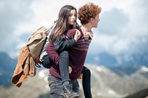 Ein Junge trägt ein Mädchen auf dem Rücken.