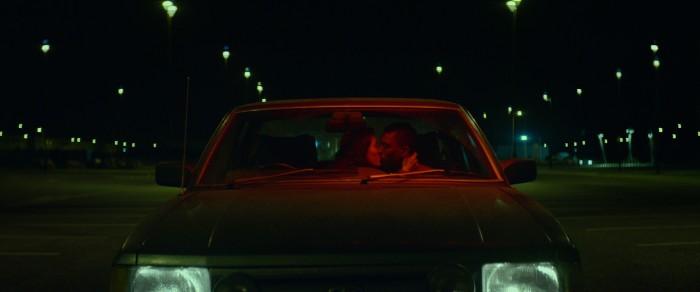 Ein küssendes Pärchen sitzt im Auto, welches auf auf einem leeren und beleuchteten Parkplatz steht.