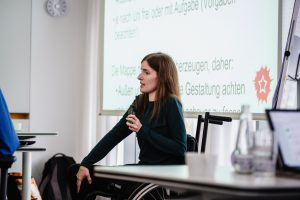 Adina Hermann referiert vorne. Sie trägt ein dunkelgrünes Oberteil, hat lange dunkelblunde Haare und hält das Mikrofon in der Hand. Sie ist mit dem Rollstuhl unterwegs. Im Hintergrund ihre Folien.