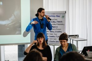 Dirk Sorge referiert. Er trägt ein hellblaues Hemd und hat lange dunkle Haare zum Zopf gebunden. Er hält das Mikrofon in der Hand und im Hintergrund ein Plakat vom Workshop sowie ein Teil seiner Präsentation zu einer Augenoperation. Im Vordergrund sitzen zwei Gebärdensprachdolmetscherinnen.