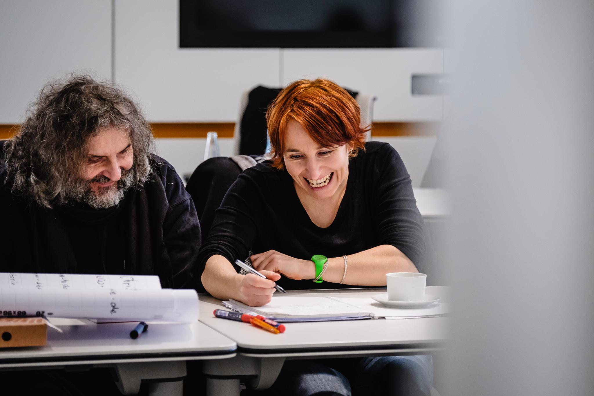 Künstler Gerald Pirner im Gespräch mit Akademieleiterin Christina Kohla. Sie schreiben auf ein Plakat ihre Ideen und lachen dabei. Gerald hat schulterlanges lockiges graues Haar und einen Vollbart, Christina kurze rote Haare. Beide tragen schwarze Pullover.