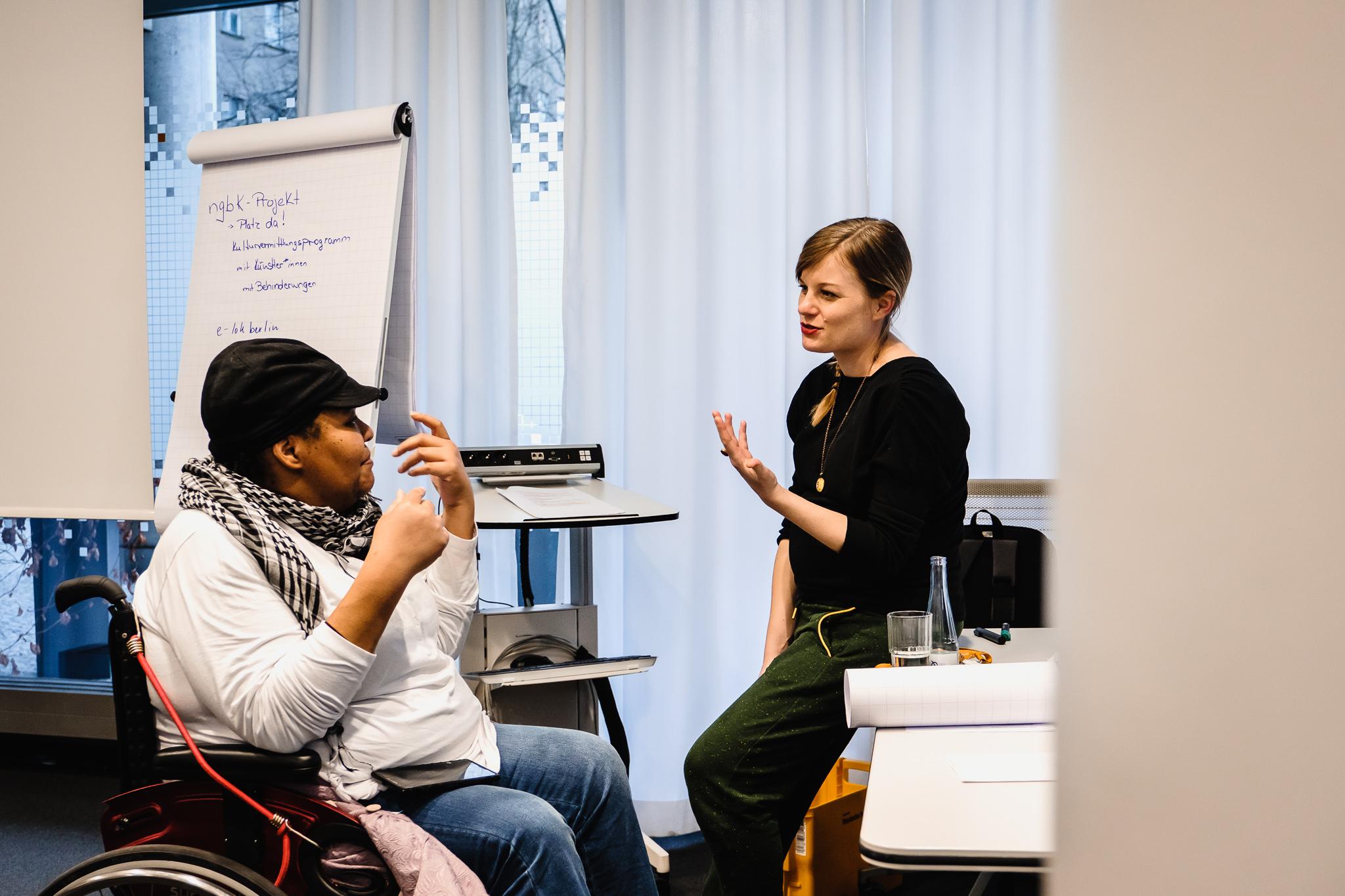 Workshop-Organisatorin Lilian Masuhr mit Teilnehmerin Nwebo Niermann im Gespräch. Nwebo trägt eine schwarze Käppi, einen weißen Pullover zu Jeans und ist mit dem Rollstuhl unterwegs. Lilian trägt einen schwarzen Pullover und eine grüne Jogginghose. Ihre blonden Haare sind zum Zopf zur Seite gebunden.