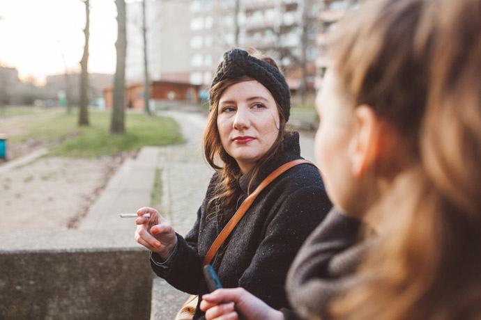 Zwei Personen sitzen nebeneinander und kommunizieren miteinander. Der Fokus liegt auf Jana Seelig. Eine junge Frau mit braunen langen Haaren, einem Stirnband, einem dunklen Mantel und Zigarette in der Hand.