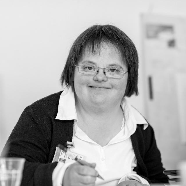 Verena Turin im Schwarzweiß-Foto. Sie hat kurze braune Haare, trägt eine Brille, eine weiße Bluse und eine schwarze Strickjacke. In der Hand hält sie einen Stift.