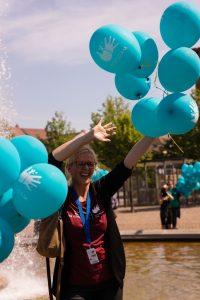 Eine Frau hält türkise Ballons in die luft
