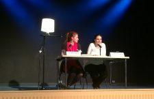 Die Autorinnen sitzen auf der Bühne am Tisch vor einem Mikro.