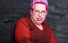 Tanja sitzt im Rollstuhl, trägt ein rotes Kleid und ein rosanes Haarband, hat rosane Haare und eine Brille.