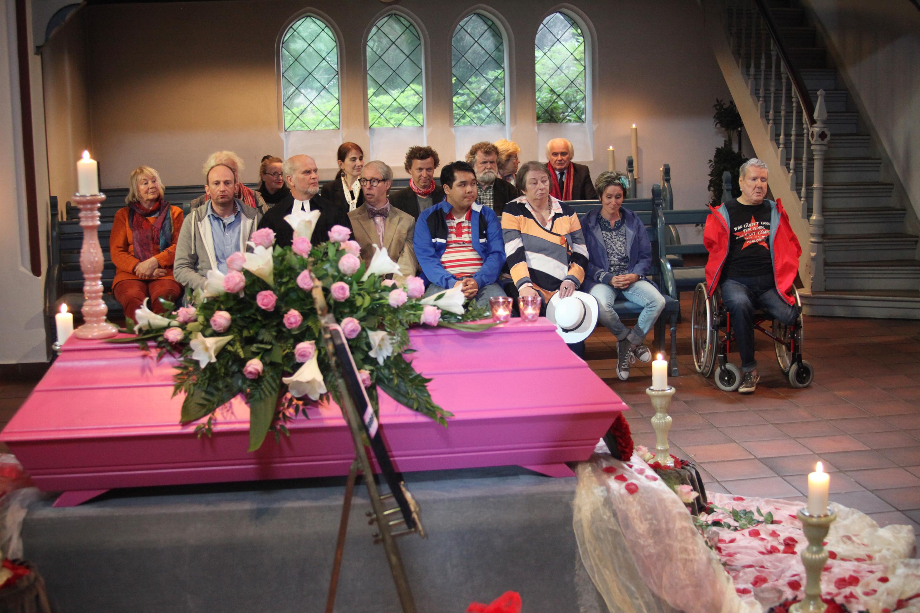 Eine Beerdingung ist zu sehen. Im Vordergrund das Grab und im Hintergrund die Gäste.