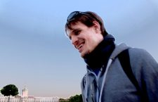 Jonas trägt einen Hoodie, einen Schal und eine Sonnenbrille auf dem Kopf. Er lächelt.