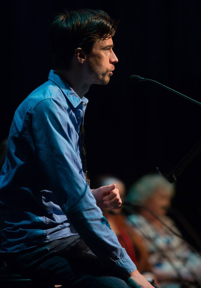 A man in his early thirties speaks into a microphone on stage. He has short brown hair and wears a blue long-sleeved shirt.