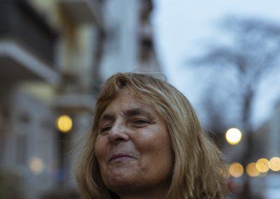 Portraitfoto einer Frau mit Mittellagen dunkelblonden Haaren. Sieht steht auf dem Bürgersteig und trägt eine dunkelblaue Jacke.