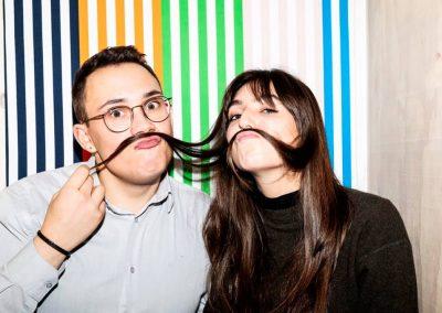 Ein Mann und eine Frau stehen vor einer bunten Wand. Sie haben die langen dunklen Haare der Frau als Schnurrbart über ihre Lippen gelegt.