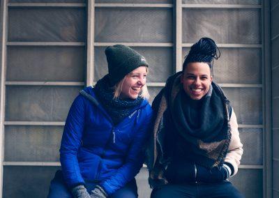 Zwei Frauen sitzen vor einem Ragel. Die Linke hat blonde Haare, trägt einen blauen Mantel und eine oliv-färbende Mütze. Die Rechte hat dunkelblaue Haare und trägt eine blau-weiße Jacke. Beide tragen Handschuhe und Schal und lachen.