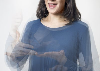 Portrait einer Frau die gerade gebärdet. Durch die Bewegung sind ihre Hände nur unscharf zu erkennen. Sie hat schulterlanges dunkles Haar, trägt eine Brille und einen blauen Pullover.