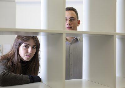 Ein Mann und eine Frau stehen hinter einem weißen Kastenregal. Sie schauen durch die Öffnungen in die Kamera.