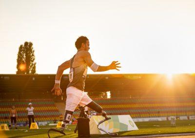 Ein Leichtathlet mit zwei Beinprothesen rennt im Stadion von links nach rechts an der Kamera vorbei. Er trägt eine kurze weiße Hose und ein Trainingsleibchen er wird von der untergehenden Sonne angestrahlt.