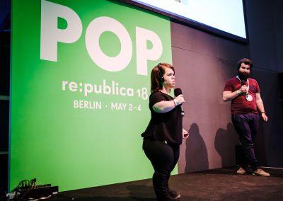 """Ein Mann und eine Frau stehen mit einem Mikrophon auf der Bühne. Im Hintergrund ist ein hellgrünes Plakat auf dem """"POP er:publica """" in weißen Buchstaben steht."""