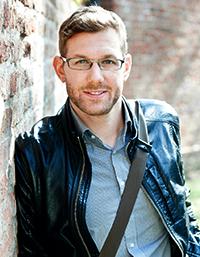 Thomas Mitterhuber trägt eine schwarze Lederjacke und ein hellblaues Hemd. Er hat kurze blonde Haare und eine Brille.