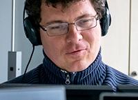 Henning Schmidt trägt Kopfhörer und schaut auf den Bildschirm vor ihm