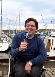 Holger Kiesel sitzt im Rollstuhl und spricht ins Mikro. Im Hintergrund sind Schiffe zu sehen.