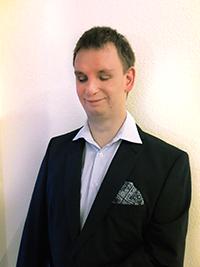 Thorsten trägt Anzug und Hemd. Er lächelt, hat aber die Augen geschlossen.