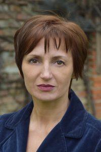 Die Autorin Lerchbaum im Profil. Sie hat braune Haare und braune Augen und schaut ernst.
