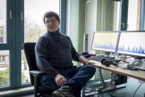 Henning sitzt an einem Schreibtisch mit Schnittmonitoren
