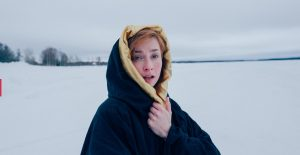 eine frau ist in einer schneelandschaft zu sehen. sie schaut verzweifelt an der kamera vorbei und trägt einen großen dicken mantel mit kapuze.
