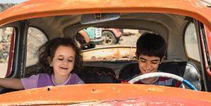 zwei kleine kinder sitzen in einem schrottauto vorne am steuer und beifahrersitz. sie lachen.