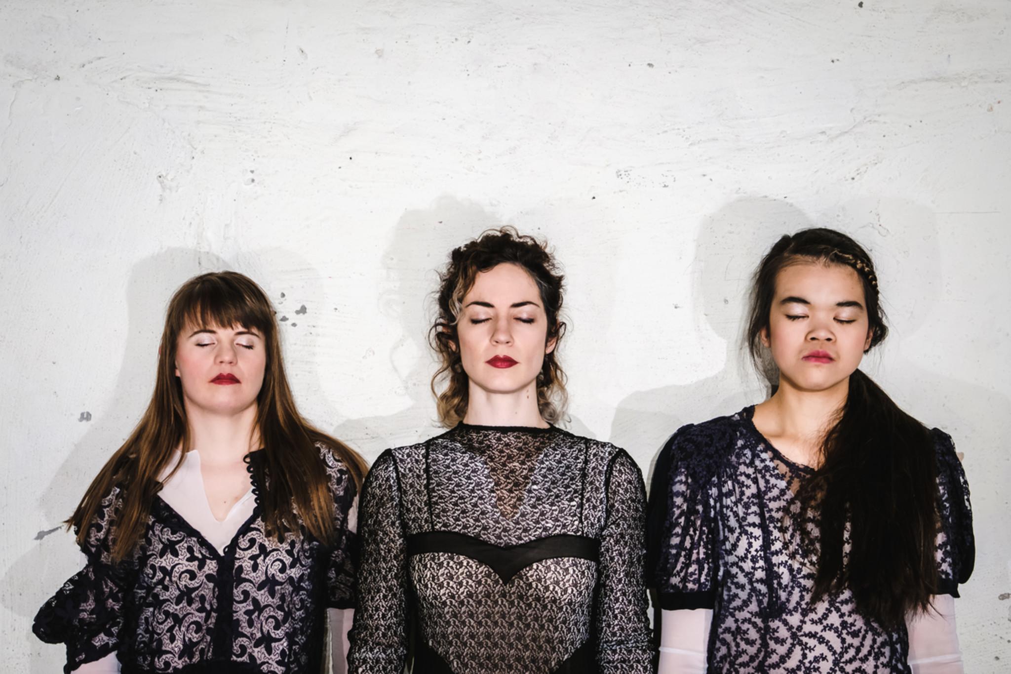 Drei Frauen stehen nebeneinander, alle haben die augen geschlossen.