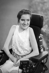 Ein schwarz-weiß Foto von Laura Mench. Sie hat dunkle mittellange Haare und hat ein helles ärmelloses Kleid an.