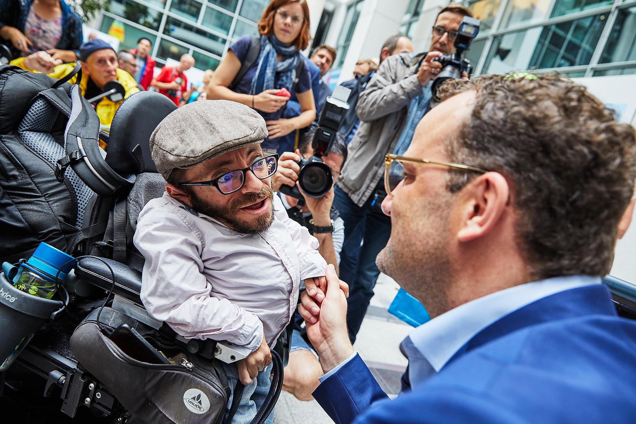 ein mann im rollstuhl und ein nichtbehinderter mann begegnen sich, einer geht in die hocke
